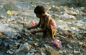 An Indian child searches for valuables in a garbage dump in New Delhi October 3, 2005. About 30 percent of India's more than one billion people live below the official poverty line. Picture taken on October 3, 2005. REUTERS/Adnan Abidi