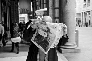 A man is reading a newspaper in the street of Milan.